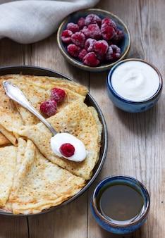 Pfannkuchen mit saurer sahne, himbeeren und honig. das traditionelle gericht über karneval und maslenitsa.