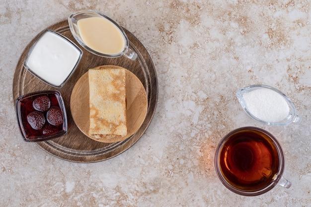 Pfannkuchen mit saurer sahne und einer tasse tee