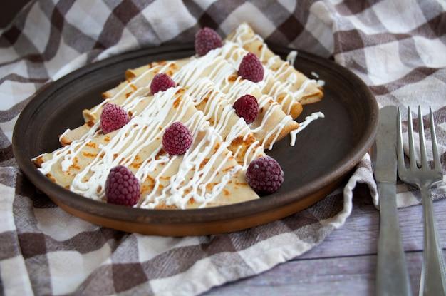 Pfannkuchen mit saurer sahne und himbeere. leckeres frühstück zu hause.