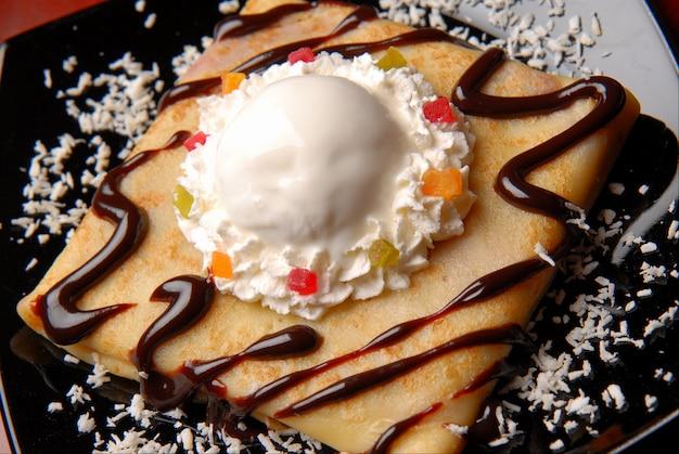 Pfannkuchen mit schokolade und eiscreme, dekoriert mit schokoladenglasur und kandierten früchten