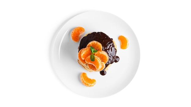Pfannkuchen mit schokolade und mandarinen lokalisiert auf weiß.