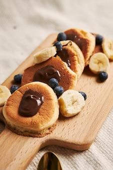 Pfannkuchen mit schokoladensauce, beeren und banane auf einem holzteller