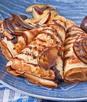 Pfannkuchen mit schokoladensirup und pflaumen