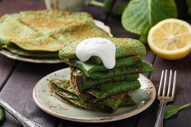 Pfannkuchen mit spinat und sauerrahm auf holztisch.