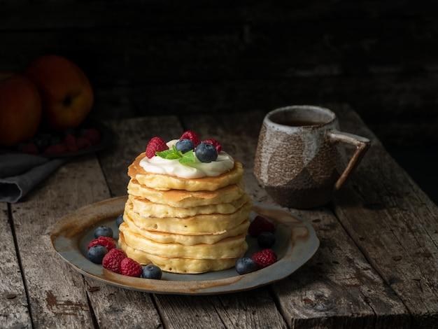 Pfannkuchen mit vanillecreme, heidelbeeren und himbeeren. dunkler schwermütiger alter rustikaler hölzerner hintergrund.