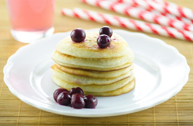 Pfannkuchen, pfannkuchen auf einer platte mit der kirsche, die das café ausfüllt. horizontale fotografie