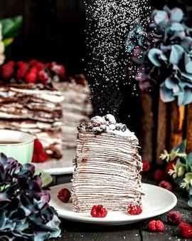 Pfannkuchen-schokoladenkuchen mit himbeeren, bestreut mit puderzucker