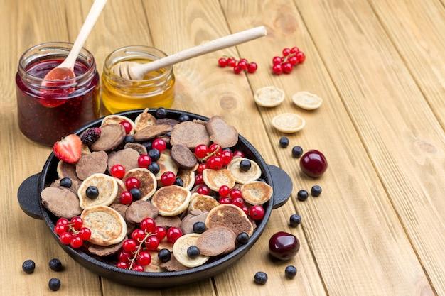 Pfannkuchen und beeren in der pfanne. honig und marmelade auf dem tisch. helle holzoberfläche. draufsicht. speicherplatz kopieren