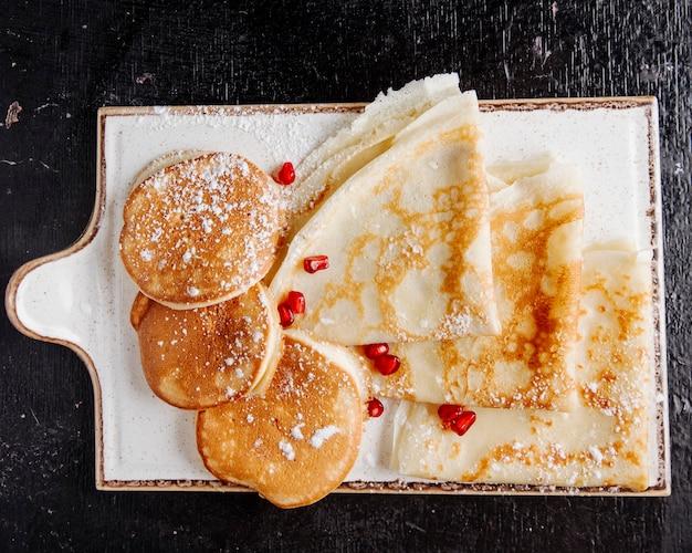 Pfannkuchen und crepes mit puderzucker und granatapfel in der draufsicht