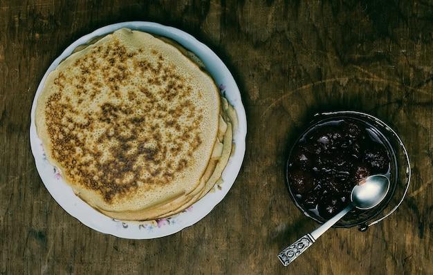 Pfannkuchen und marmelade auf altem holzhintergrund