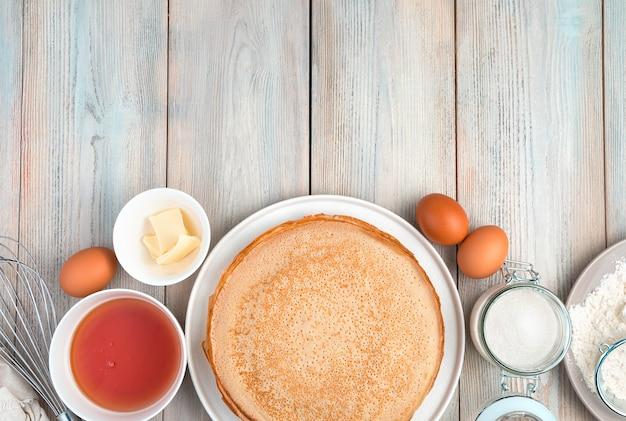 Pfannkuchen und zutaten zum kochen auf einem hellen hölzernen hintergrund. draufsicht mit platz zum kopieren. konzept der kulinarischen hintergründe, maslenitsa.