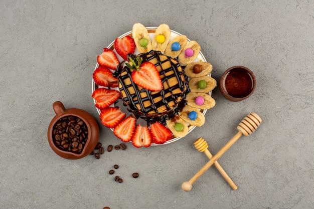 Pfannkuchen von oben mit frischem obst und schokolade auf dem grauen boden