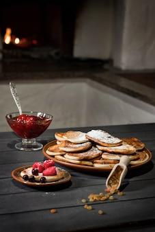 Pfannkuchen werden mit puderzucker auf einem teller bestreut.