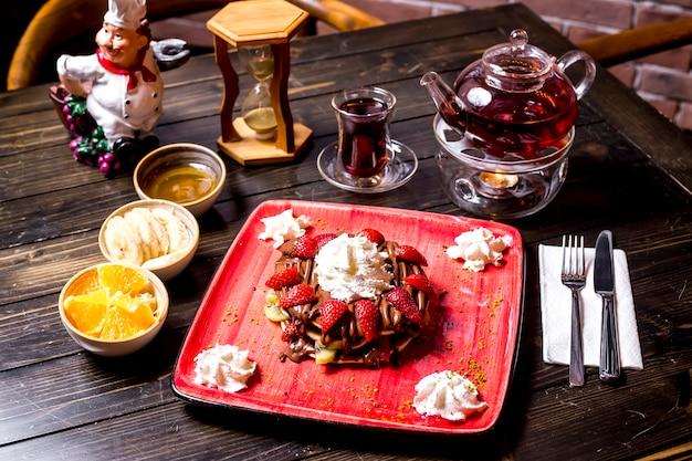 Pfannkuchencreme erdbeer-schokoladensauce früchte und teekanne seitenansicht
