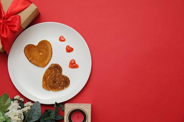Pfannkuchenherz formte auf weiße platte, zusammensetzung für valentinstag mit lebensmittel. platz für text