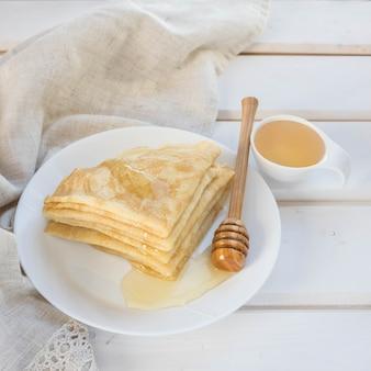 Pfannkuchenhonig und hölzerner honiglöffel auf einem weißen teller