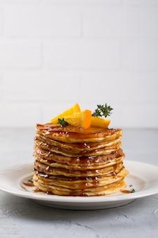 Pfannkuchenstapel mit orangen- und karamellsirup bestreuen