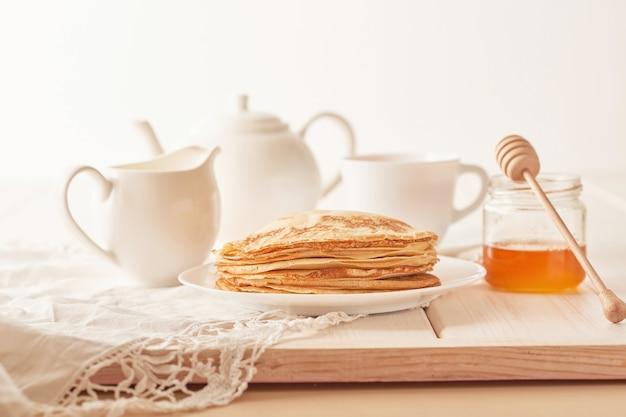 Pfannkuchenwoche: pfannkuchen mit honig und tee auf dem tisch