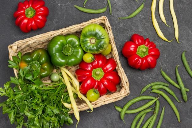 Pfeffer, grüne tomate und petersilie im weidenkorb. rote paprika und grüne bohnen auf dem tisch. flach liegen. schwarzer hintergrund
