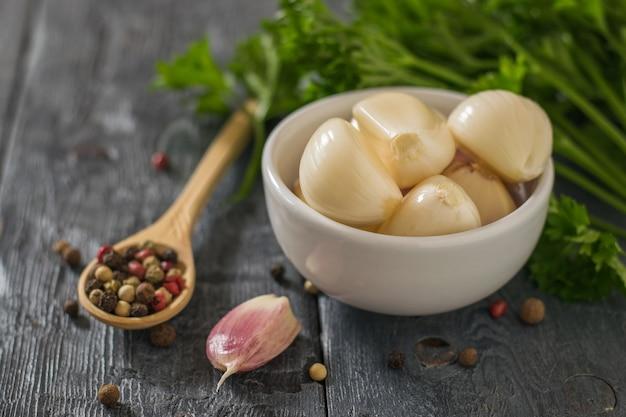 Pfeffer in einem holzlöffel und geschälten knoblauch in einer schüssel auf einem holztisch. gesunde natürliche gewürze. bestandteil der traditionellen medizin.