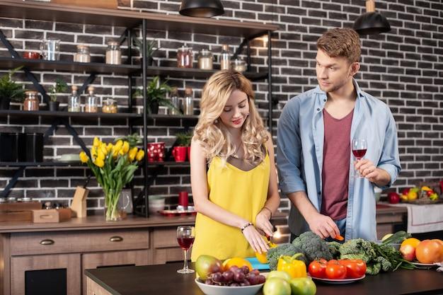 Pfeffer schneiden. blonde schöne fürsorgliche frau, die pfeffer für salat schneidet, der in der nähe ihres mannes steht standing