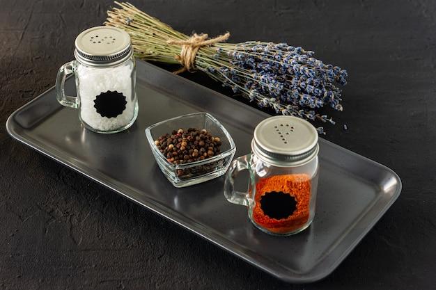 Pfeffer- und salzglasschüttler auf schwarzem beton-backgroun mit kopierraum.