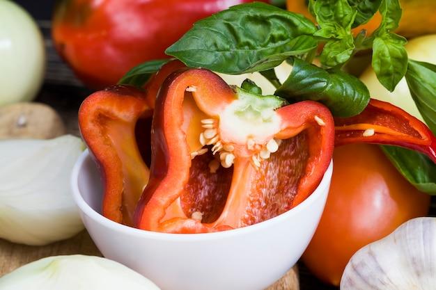 Pfeffer, zwiebel, zucchini, knoblauch und anderes gemüse auf dem küchentisch, kochen und salate aus natürlichem und frischem gemüse. gemüse wird nicht alle gewaschen und von schmutz befreit