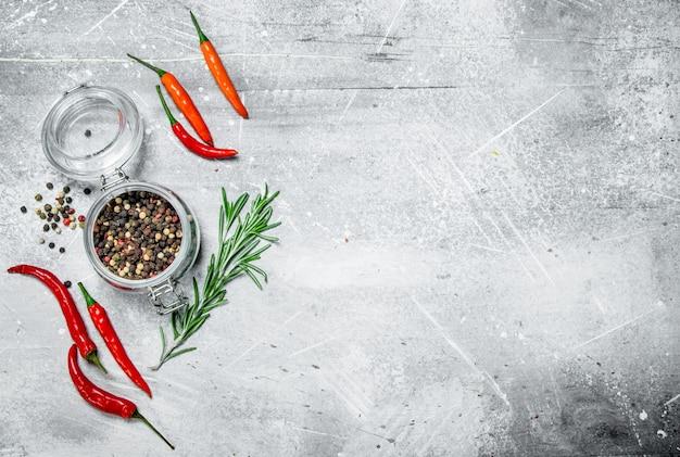 Pfeffererbsen in einem glas mit paprika und rosmarin auf rustikalem tisch.