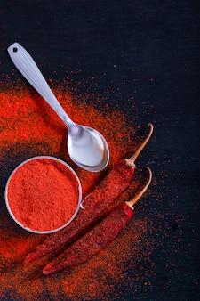 Pfefferflocken des roten paprikas und chilipulver sprengten auf schwarzem hintergrund