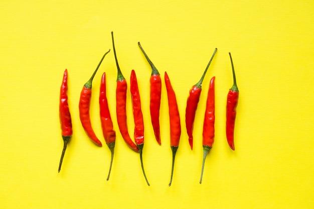 Pfefferhülsen des roten paprikas auf hellem gelbem hintergrund