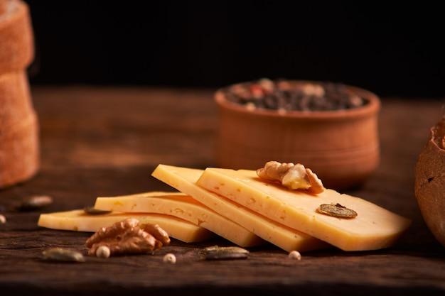 Pfefferkörner in einer hölzernen schüssel auf tabelle mit käse.