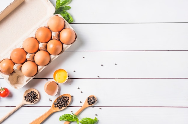 Pfefferkorn auf hölzernem löffel mit basilikumblatt und eiern im karton