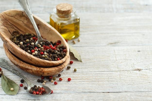 Pfefferkornmischung in einer schüssel, lorbeerblättern und olivenöl auf einem holztisch