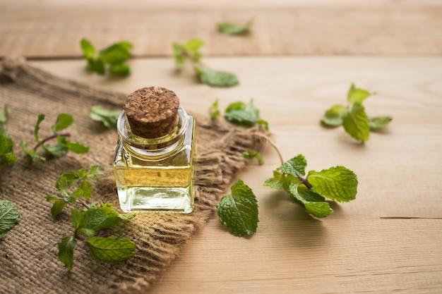 Pfefferminze ätherisches öl in glasflasche mit minze auf holz hintergrund kraut oder aromatherapie spa-konzept