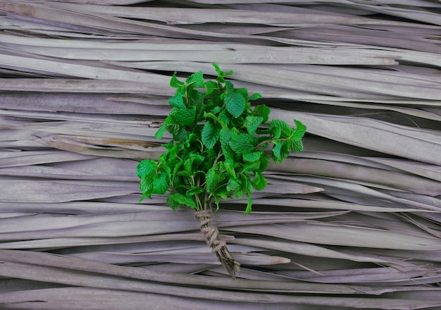 Pfefferminzstiele mit jute-seilbindung flach auf trockenem palmblattmuster-texturhintergrund