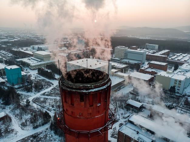 Pfeife mit rauch. wärmeenergienetz. kwk kraft-wärme-kopplung, ein system, bei dem dampf, der in einem kraftwerk als nebenprodukt der stromerzeugung erzeugt wird, zur beheizung von gebäuden in der nähe verwendet wird.
