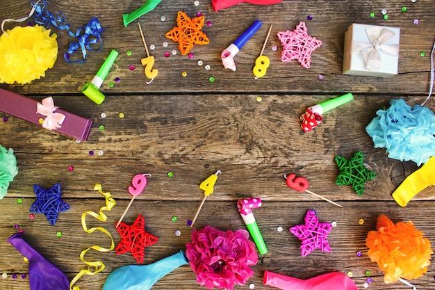 Pfeifen, ballongeschenke, kerzen, dekoration auf altem hölzernem hintergrund. konzept der geburtstagsfeier der kinder. ansicht von oben flach legen