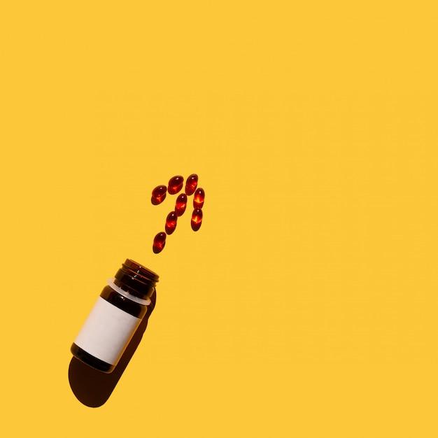 Pfeil von vitaminen, verschüttend aus einer flasche auf gelbem hintergrund heraus. ansicht von oben.