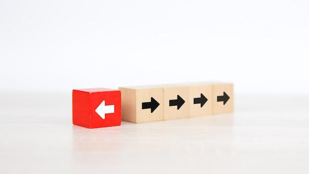 Pfeilsymbol auf würfelförmigem holzspielzeugblock mit dem zeigen in entgegengesetzte richtungen.