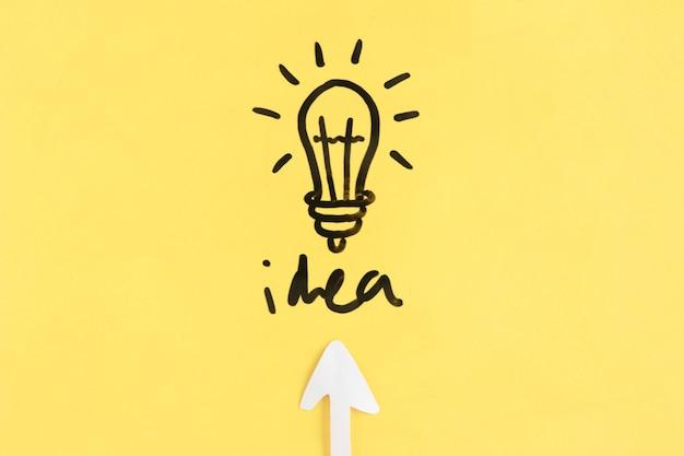 Pfeilsymbol, das in richtung zur glühlampe mit ideenwort verweist