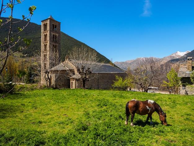 Pferd, das am fuß einer kirche weiden lässt