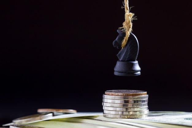Pferd oder könig des schachs führen durch, indem sie an der dollarbanknote und -münze im dunkelheitshintergrund hängen.