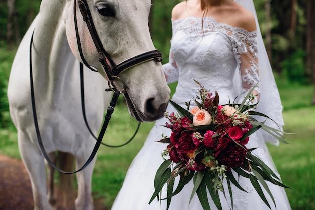Pferd schnüffelt einen blumenstrauß in den händen der braut