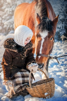 Pferd späht in den korb eines kleinen mädchens in antiken kleidern winter frostigen sonnigen tag.