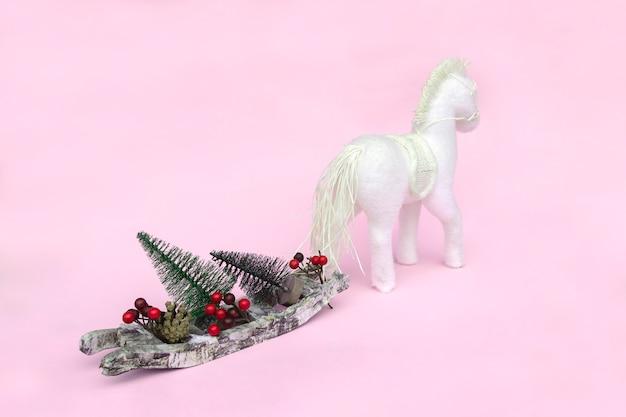 Pferd trägt schlitten mit weihnachtsbäumen, zapfen, bällen
