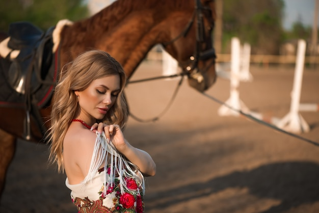 Pferd und frau in einem schal auf der ranch