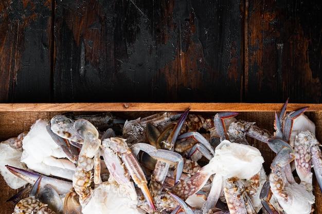 Pferdekrabbe, blaue krabbe, blumenkrabbe gefroren in eisset, in holzkiste, auf dunklem holzhintergrund, draufsicht flach gelegt, mit copyspace und platz für text