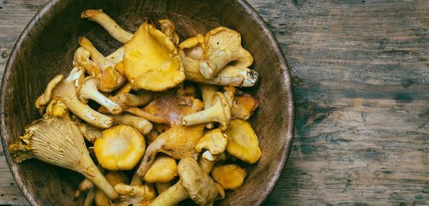 Pfifferlingspilze auf einem hölzernen hintergrund. rohe pilze in einer hölzernen schüssel.