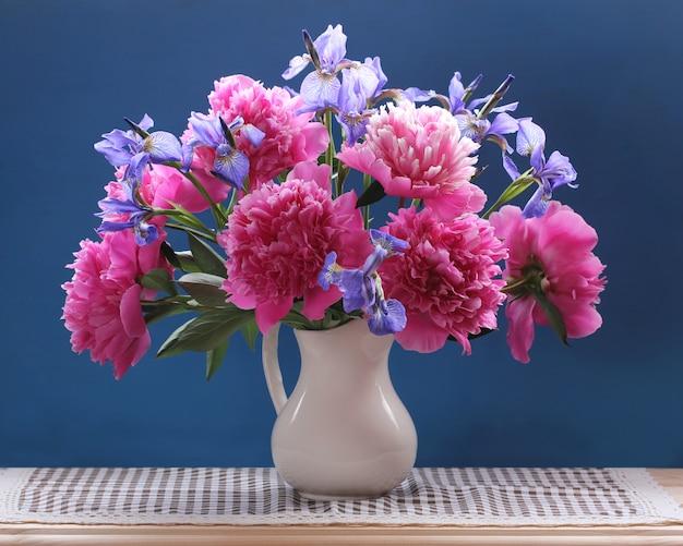 Pfingstrosen und iris. schöner blumenstrauß von gartenblumen in einem krug