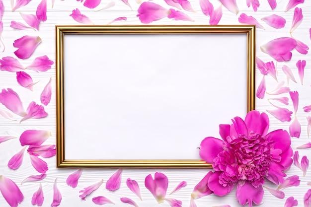 Pfingstrosenblume und blütenblätter und ein goldrahmen auf einem weißen hölzernen hintergrund